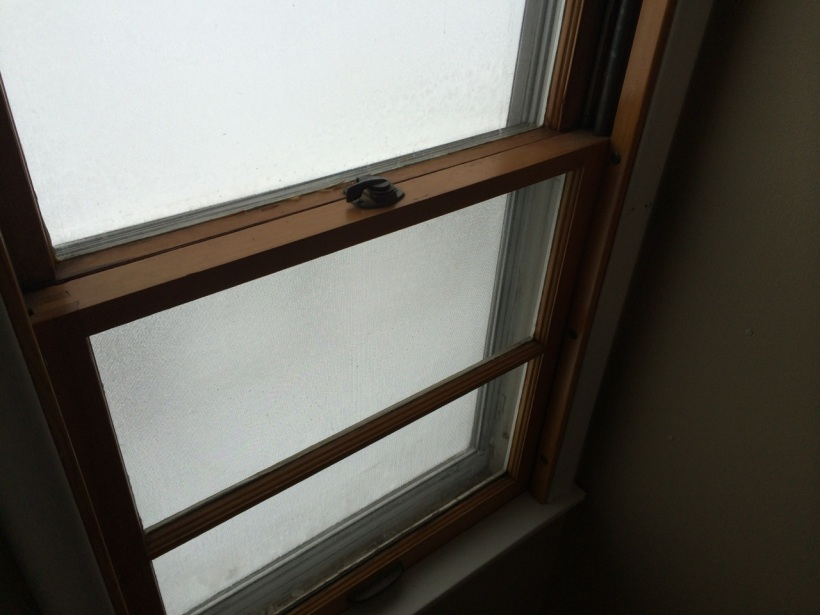 Old double hung window covered with frost